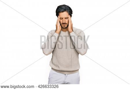 Young hispanic man wearing casual clothes suffering from headache desperate and stressed because pain and migraine. hands on head.