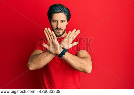 Young hispanic man wearing casual red t shirt rejection expression crossing arms doing negative sign, angry face