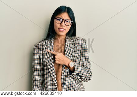 Young chinese woman wearing business style and glasses pointing aside worried and nervous with forefinger, concerned and surprised expression