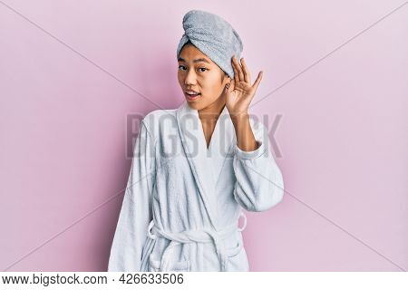 Young chinese woman wearing shower towel cap and bathrobe smiling with hand over ear listening an hearing to rumor or gossip. deafness concept.