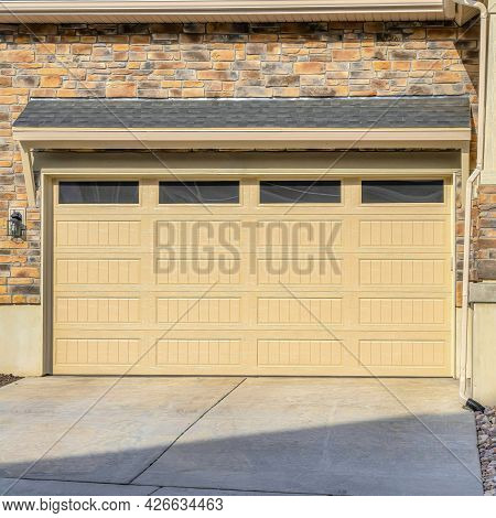 Square Glass Paned Front Door And Wide Garage Door Of Home With Driveway And Stairs