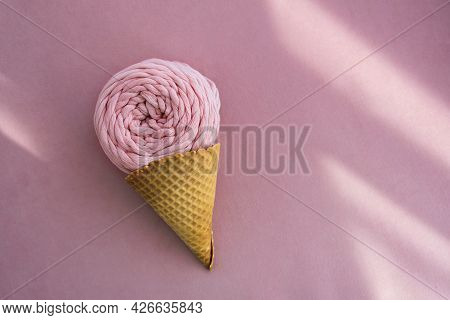 Top View Of Pink Macrame Yarn Skein In Ice Cream Waffle Cone On A Pink Background With Sunlight Beam