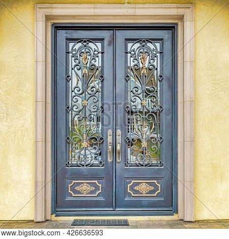 Square Double Door With Decorative Wrought Iron And Glass Panes At The House Entrance