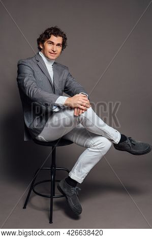Tall Handsome Man Dressed In White Turtleneck, White Jeans And Grey Jacket Sitting On Chair And Posi