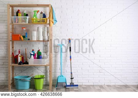 Shelving Unit With Detergents, Cleaning Tools And Toilet Paper Near White Brick Wall Indoors. Space