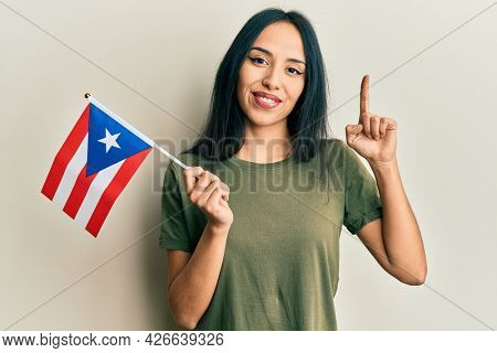 Young hispanic girl holding puerto rico flag smiling with an idea or question pointing finger with happy face, number one