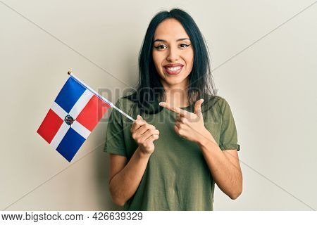 Young hispanic girl holding dominican republic flag smiling happy pointing with hand and finger