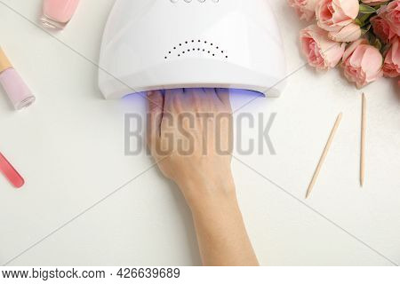 Woman Using Ultraviolet Lamp To Dry Gel Nail Polish At White Table, Top View