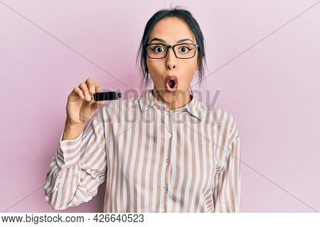 Young hispanic girl holding removable memory usb scared and amazed with open mouth for surprise, disbelief face