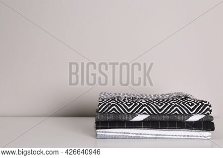 Stack Of Soft Kitchen Towels On White Countertop Near Wall, Space For Text