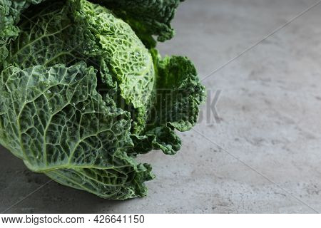Fresh Ripe Savoy Cabbage With Water Drops On Grey Table, Closeup. Space For Text