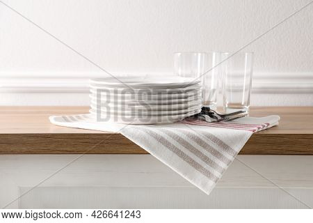 Kitchen Towel And Clean Dishware On Wooden Countertop