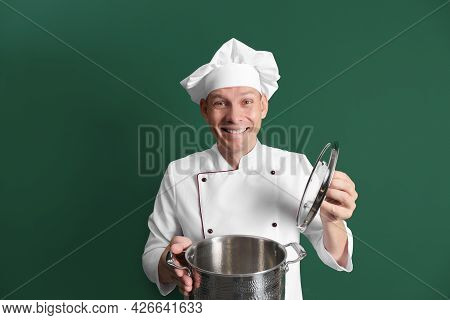 Happy Male Chef With Cooking Pot On Dark Green Background