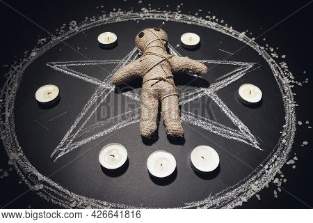 Voodoo Doll Pierced With Pins And Candles In Pentagram On Black Table