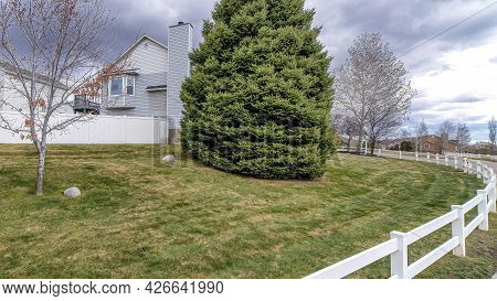 Pano Landscaped Yard Of House With Low Fence Along Road With Cloudy Sky Bakcground