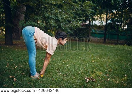 Indian Woman In Ordinary Casual Clothes Doing Yoga In Outdoor Summer Park.