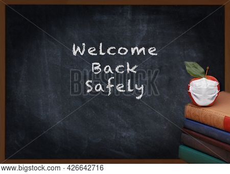 Back to School Concept. A stack of books and a red apple with a Covid-19 Mask on top in front of a chalkboard with Welcome Back Safely.