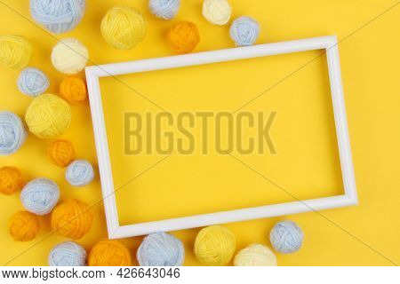 A White Empty Frame And A Lot Of Blue And Yellow Balls Of Yarn For Knitting Or Crocheting On A Yello