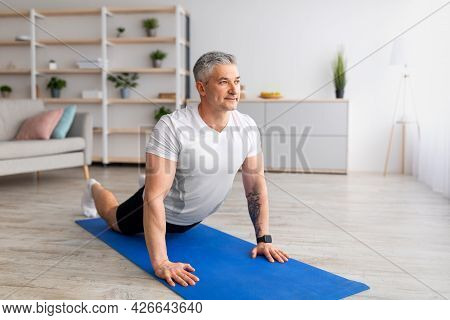 Relief Lower Back Pain. Mature Man Doing Cobra Pose, Stretching Back Muscles, Excercising In Living