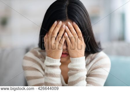 Despair Concept. Portrait Of Upset Asian Woman Covering Face With Hands