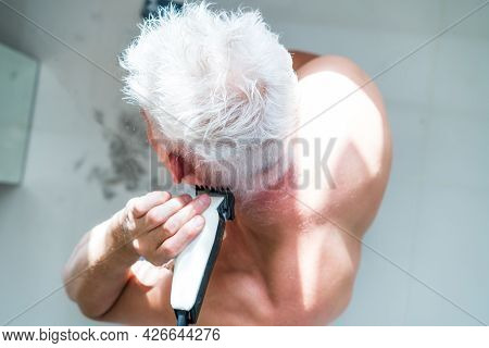 Top View White Hair Man Doing Self Haircut With A Clipper And Looks In The Mirror. Self-care At Home