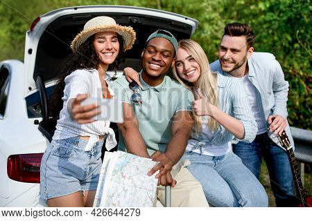 Funky Young Friends Taking Selfie On Mobile Phone During Road Trip, Sitting In Car Trunk, Traveling