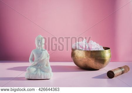 Decorative White Buddha Statuette And Tibetian Singing Bowl On Pink Background. Meditation And Relax