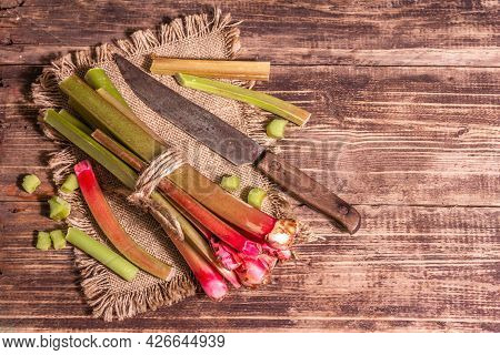 Fresh Rhubarb Stalks And Cut Pieces On A Vintage Wooden Table