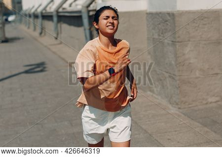 Young Indian Woman Runner Jogging In Wet Sweaty T-shirt At City Street.