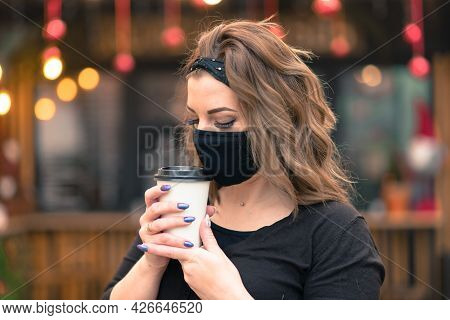 Precautions In The Public Places After Quarantine Ended. Young Woman With Medical Mask In Cafe