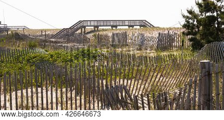 Wooden Walkways To Safely Get Over Sand Dunes And Picket Fences With Green Brush Protecting Fire Isl