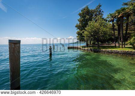 Coastline In Front Of The Small Town Of Garda, Tourist Resort On The Coast Of Lake Garda (lago Di Ga