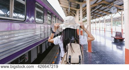 At The Train Station. Traveler Woman Tourist Hand Holding Hat And Backpack Taking The Train To Trave