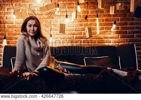 Beautiful Woman Sitting On Couch. Christmas And New Year Atmosphere. Light Bulbs And Present Boxes B