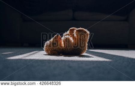Teddy Bear Is Laying Down On Carpet In Cinematic Tone, Dramatic Shot Of Lonely Teddy Bear Laying Dow