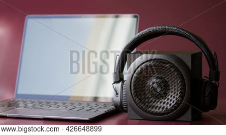 A Square Black Audio Speaker And Wireless Headphones Next To A Slim Modern Laptop. Concept For Digit
