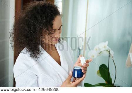 Beautiful African American Woman In A White Bathrobe In The Bathroom Opens A Jar Of Moisturizer