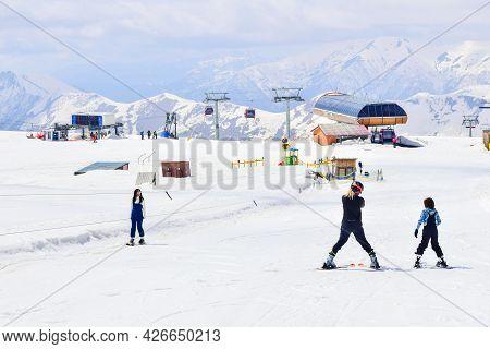 Caucasian Ski Instructor Teaching Teenager To Ski In Gudauri Ski Resort. Ski Holiday In Georgia