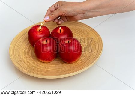 A Woman's Hand Brings A Lighted Match To The Candles In The Form Of Red Apples, Beautifully Lights T