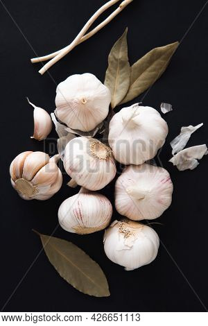 Aromatic Garlic Bulbs With Spices, Bay Leaves And Peppercorns On A Black Background. Condiments And