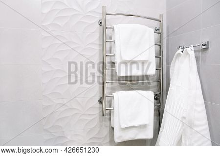 White Towels And A Bathrobe Hang In The Bathroom. Bathroom Interior In A Hotel Room, Apartments. Hea