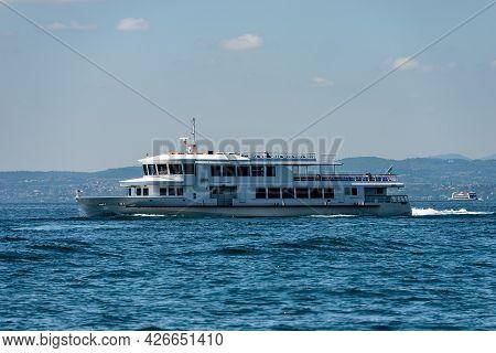 Ferry Boats In Motion In Front Of The Small Village Of Bardolino On Lake Garda (lago Di Garda), Vero