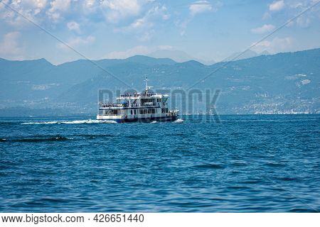 Ferry Boat In Motion In Front Of The Small Village Of Bardolino On Lake Garda (lago Di Garda), Veron