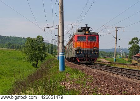 Red Old Freight Train Or Locomotive On Trans-siberian Railway Along Russian Village In Siberia