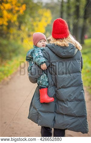 A Walk In The Park With A Toddler, Mom Carries A Child In Her Arms Down The Street, View From The Ba