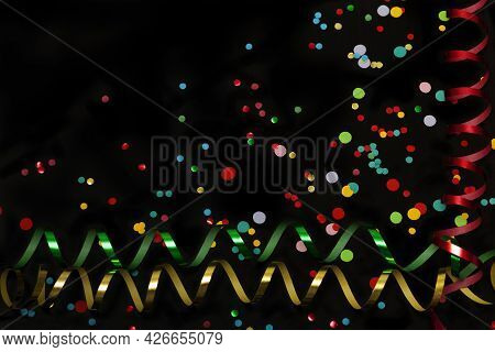 Horizontal Photo Of Colorful Confetti And Paper Streamers On Black Background With Space For Text.