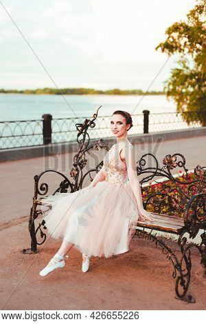 Smiling Happy In A Pink Silk Dress Sits On A Wrought-iron Bench In A Park On The River Bank At Sunse
