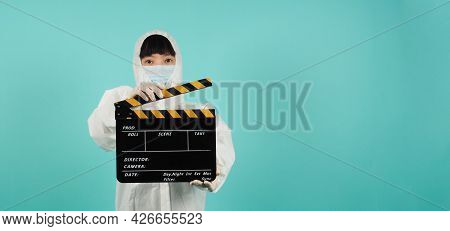 Black Cand Yellow Clapperboard Or Movie Slate.asian Woman Wear Face Mask And Ppe Suit On Mint Green