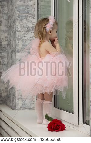 A Little Funny Girl In A Smart Pink Dress And High-heeled Shoes Looks Out The Window.