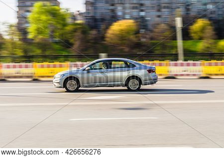 Moscow, Russia - May 2021: Side View Rolling Shot With Silver Car In Motion. Vehicle Driving Along T